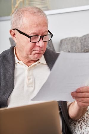 Retiree or pensioner holding a letter and checking finance bills