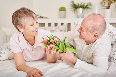 Senior man gives flowers to wife for her birthday or valentines day