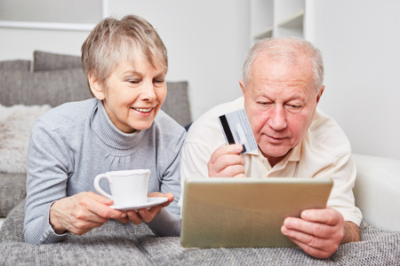 Online shopping concept with senior couple using tablet computer