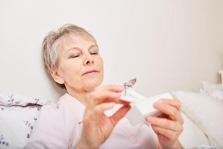 Sick senior citizen holding pill dispenser with medication Stock Photo
