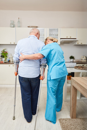 Physiotherapy or physical therapy for senior man with crutches Stock Photo
