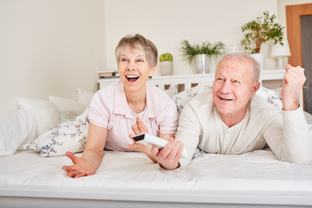 Senior couple watching TV in bed