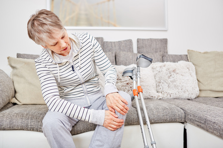 Senior woman with crutches and knee injury has pain