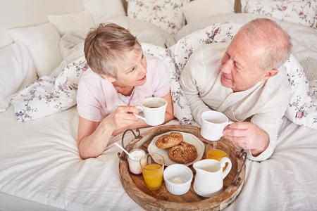 Seniors having room service breakfast in their bedroom Stock Photo