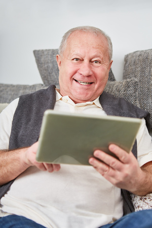 Modern senior man holds tablet with joy and learns about online communication