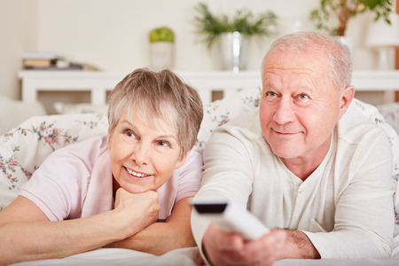 Senior couple watch TV for leisure and relaxation in their free time