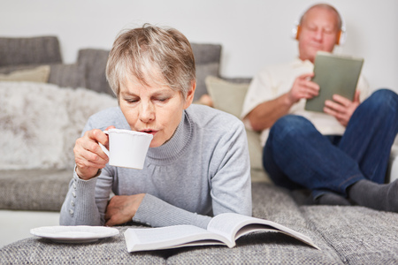 Senior woman drinking cup of coffee and reading book at home
