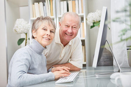 Happy senior couple together at place of work with computer