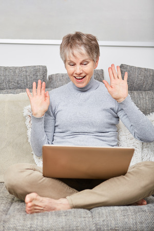 Senior woman has fun with video chat and smiles and waves with joy