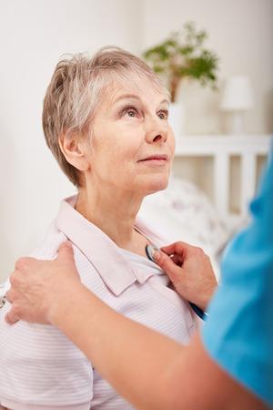 Nurse examine senior woman with dementia using stethoscope