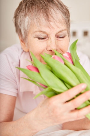 Happy senior woman with flowers bouquet gift Stock Photo
