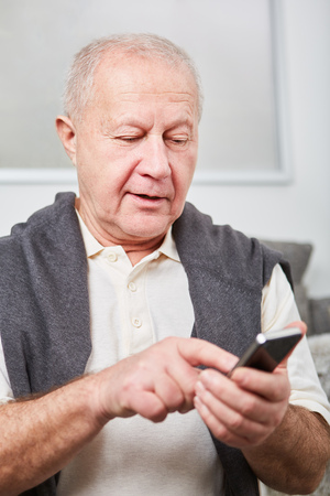 Senior typing message on smartphone as modern man