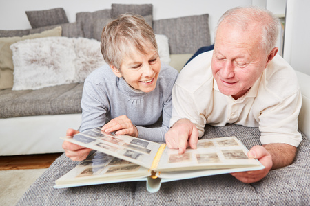Senior citizens with photo album looking at photos as reminder