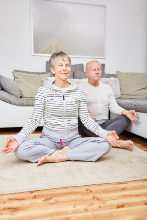 Senior couple practice yoga at home for meditation