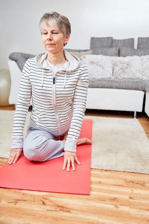 Active senior woman making gymnastics exercise at home