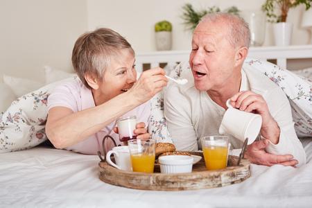 Happy seniors having breakfast in bed together in romanctic pension