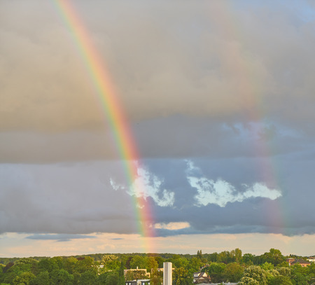 Strong rainbow after bad weather in the sky over a city Stock Photo
