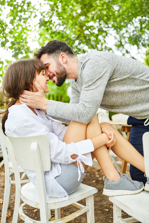 Young man lovingly kisses his girlfriend in the garden in summer Stockfoto - 102243341