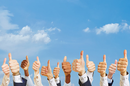 Business thumbs up signs under the sky as motivation Stock Photo