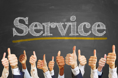 Business thumbs up in front of saying service on blackboard