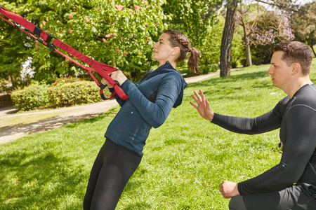 Woman with Personal Trainer at the park sling training Stok Fotoğraf