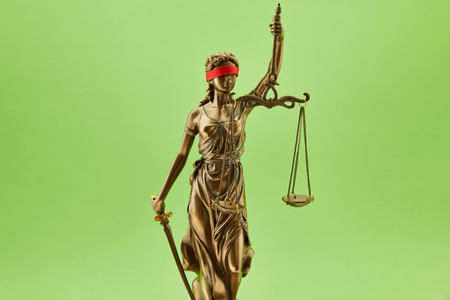 Blind Justitia statue as justice concept in front of a green background