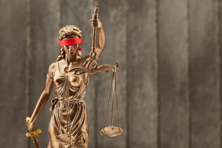 Justitia statue as law and law concept in front of a wood background