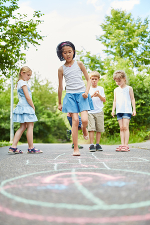 Active girl and friends playing hopscotch competition for leisure