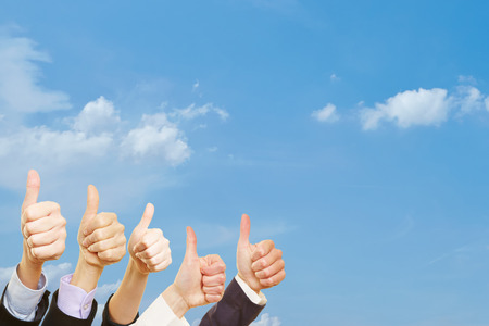 Business people are holding thumbs up underneath a blue sky