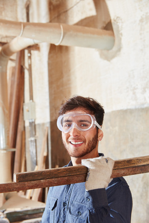 Worker at carpentry shop smiling and carrying wood