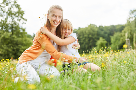 Mother is lovingly hugging by girls on a summer meadow Stockfoto - 103439677