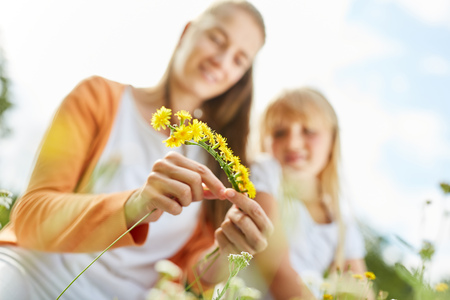 Woman binds a flower wreath in spring from dandelion flowers