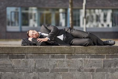 Exhausted businessman is sleeping outdoor on a wall Standard-Bild