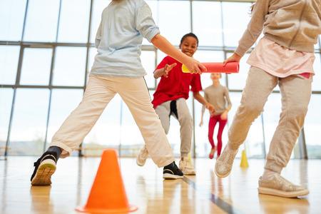 Drużyna dziecięca organizuje sztafetę w ramach wychowania fizycznego na sali gimnastycznej Zdjęcie Seryjne