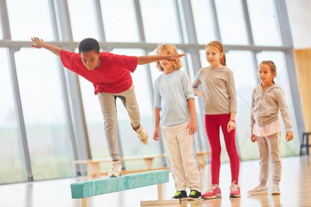 Kinderen sporten op school en balanceren op een evenwichtsbalk