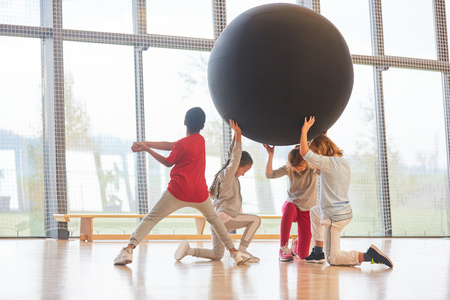 Sporty pupils raise a huge ball in the gym in teamwork