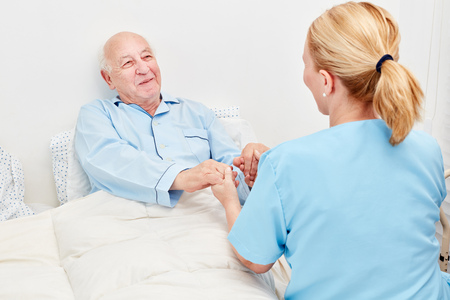 Nurse holds the hands of a senior as a patient in the hospital 写真素材