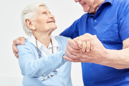 Two seniors hold hands happily and lovingly and dance Stockfoto
