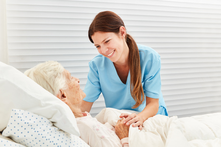 Caring geriatric nurse cares for ill senior citizen in nursing home or hospice 版權商用圖片 - 103952259