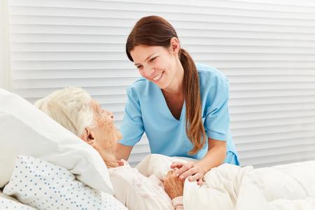 Caring geriatric nurse cares for ill senior citizen in nursing home or hospice
