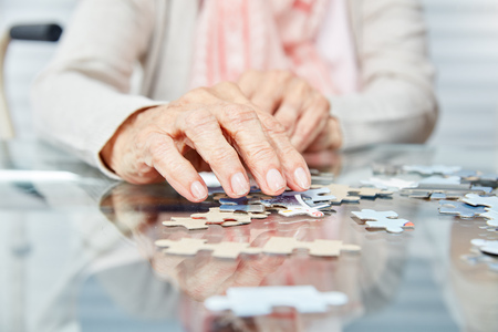 Hands of seniors playing puzzle as dementia prevention in retirement home