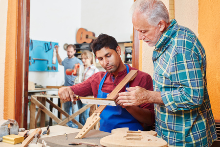 Apprentice of luthier learns with master how to build a guitar
