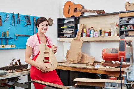 Femme comme luthier montrant une guitare en bois faite à la main