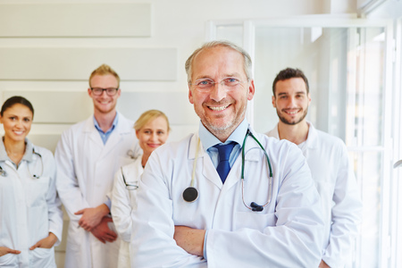 Successful doctor or physician with team at hospital