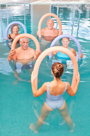 Group of seniors is doing exercises in an aqua fitness course in the swimming pool