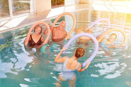 Anziani di gruppo in acquagym presso la piscina dell'hotel durante una vacanza benessere Archivio Fotografico