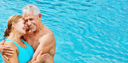 Two enamored seniors as a couple at hotel swimming pool on vacation in summer