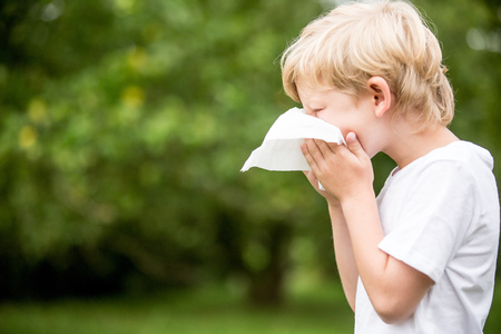 Sick child with a cold sneezing in the nature