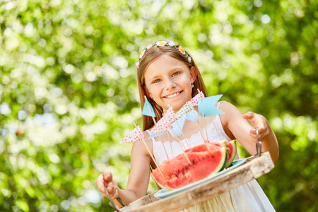 Smiling girl serves watermelons as a snack on kids birthday Foto de archivo