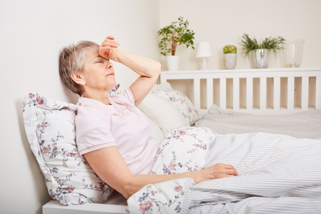 Senior woman with disease lie on bed with headache